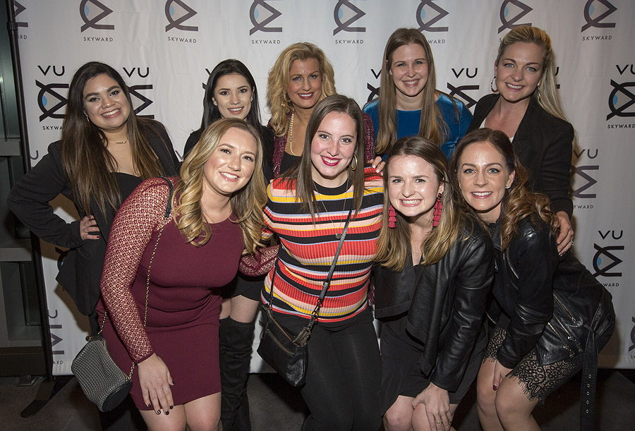 Women smiling in front of step and repeat